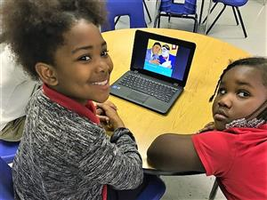 Two students watching an educational video on a computer